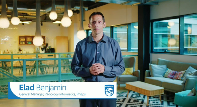 Elad Benjamin, the General Manager, Radiology Informatics at Philips is shown on video in a room with lights and a couch.